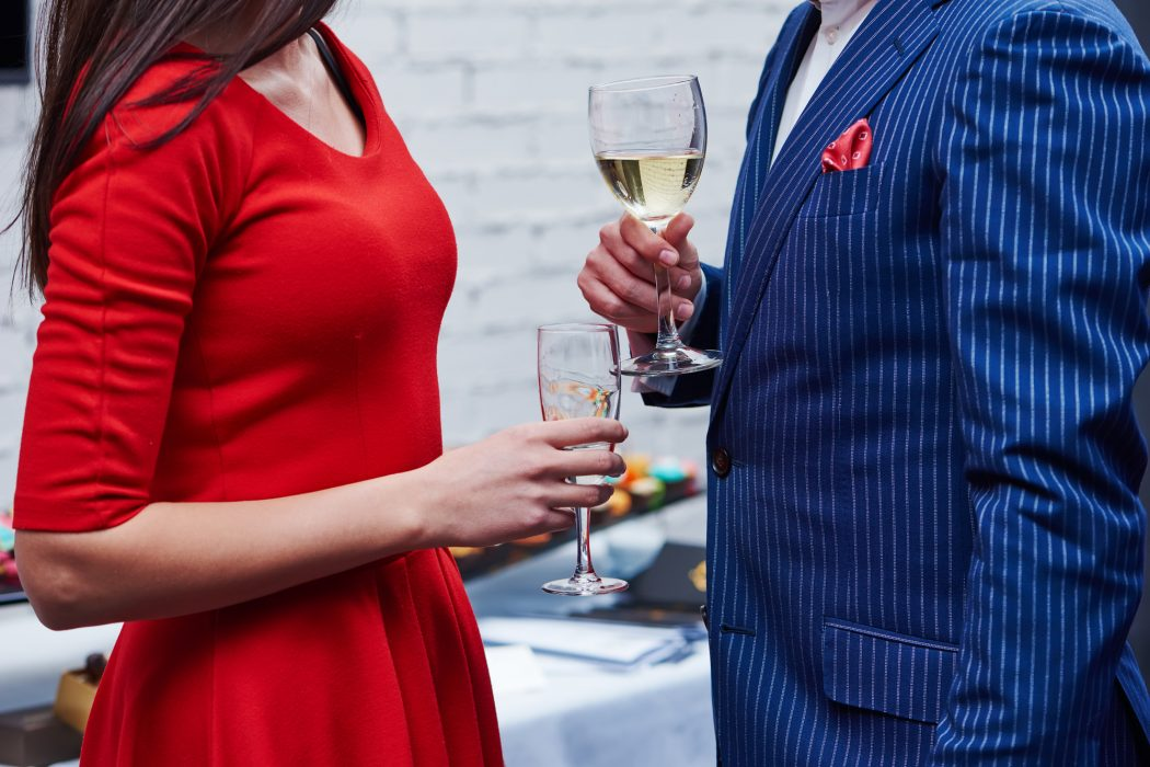 man and woman with glasses of wine at party